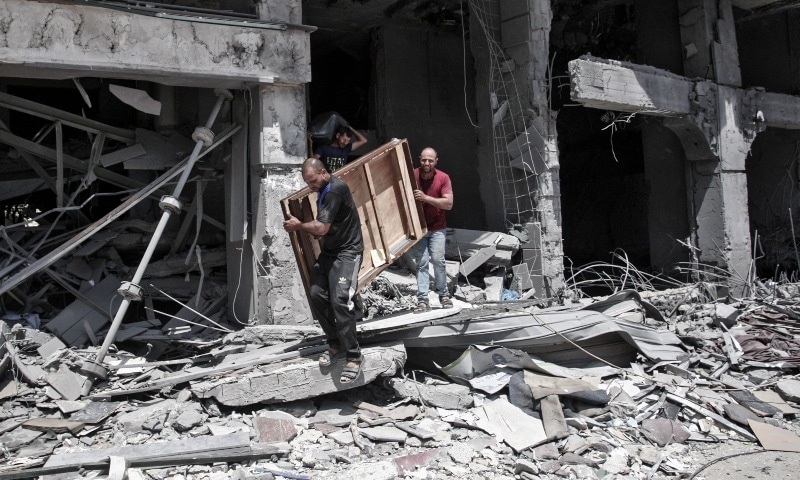 Palestinian men remove salvageable items from the bombarded Al-Jawhara Tower in Gaza City on May 17, five days after it was targeted by Israeli airstrikes. — AFP