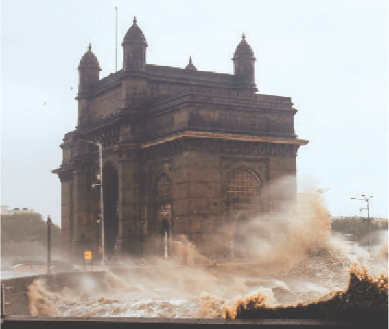 MUMBAI: Waves whipped up by cyclone Tauktae lash over the Gateway of India on Monday. [Right] Buses are stranded on a waterlogged road during heavy rain in the city. The cyclone, packing ferocious winds and threatening a destructive storm, made landfall in Gujarat, western India, late on Monday night.—AFP / AP