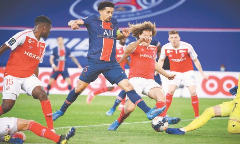 PARIS: Paris St Germain's Marquinhos (C) attempts a shot on goal during the Ligue 1 match against Stade de Reims at the Parc des Princes.—AFP