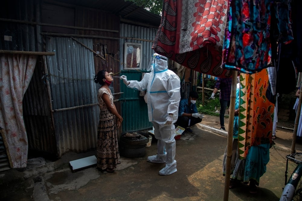 A heath worker in protective suit takes nasal swab sample of a girl to test for Covid-19 in a slum area in Gauhati on May 17. — AP