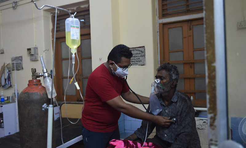 A doctor examines a Covid-19 patient in a hospital in Mahua on Tuesday. — AFP