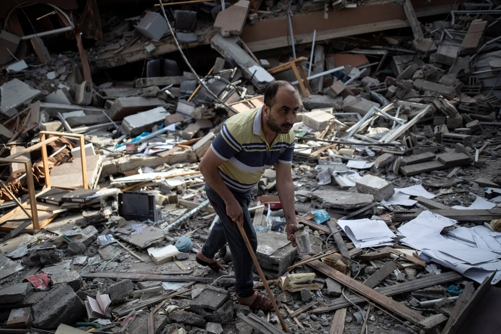 A Palestinian man inspects the damage of a house destroyed by an early morning Israeli airstrike, in Gaza City May 18. — AP