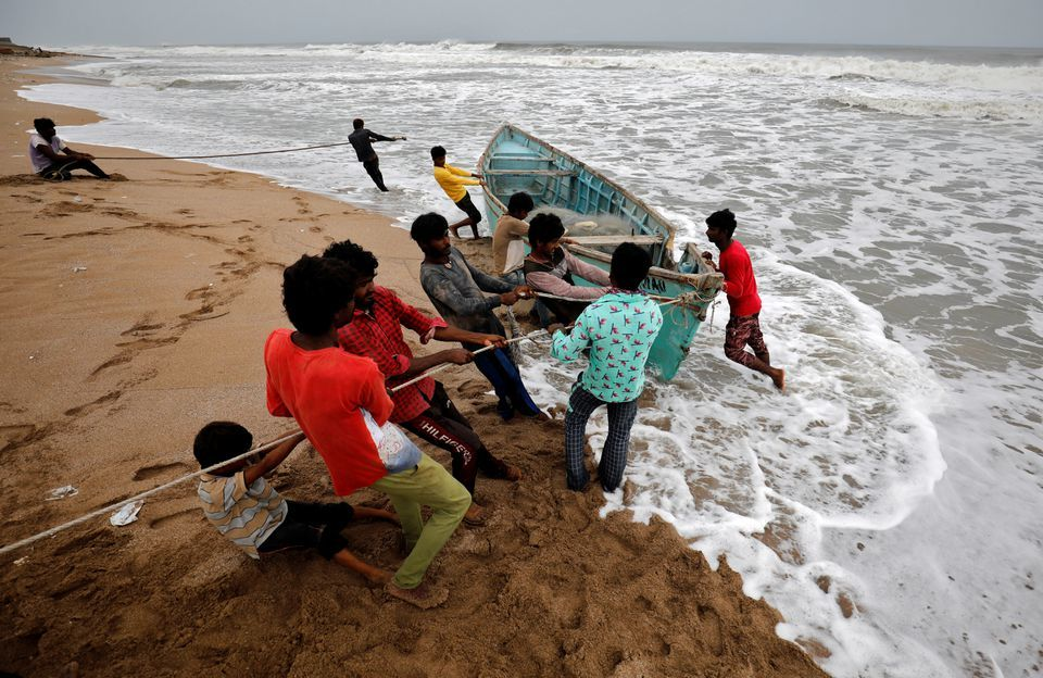 People move a fishing boat to a safer place along the shore ahead of Cyclone Tauktae in Veraval in the western state of Gujarat, India, on May 17, 2021. — Reuters