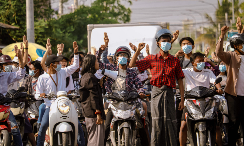 Protesters make the three-finger salute during a demonstration against the military coup in Mandalay. — AFP