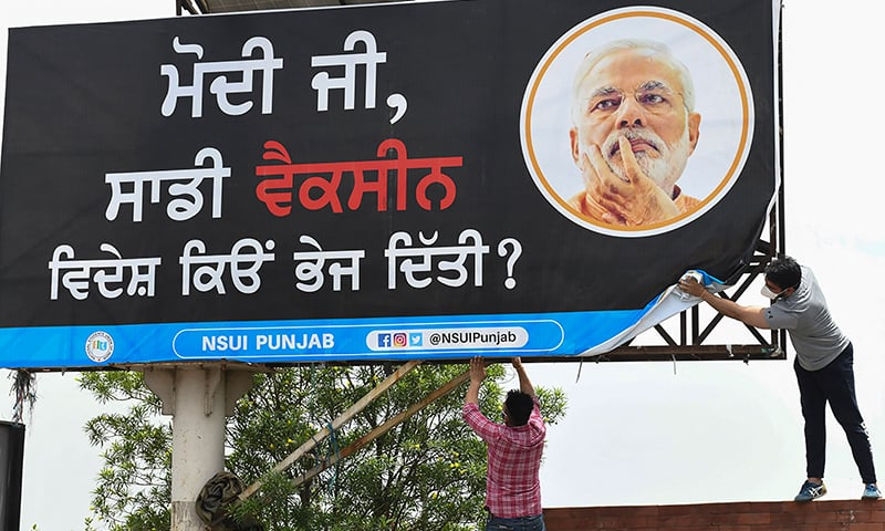 """Activists of the National Students' Union of India (NSUI) place a banner on a billboard with a picture of India's Prime Minister Narendra Modi and a message in Punjabi reading """"Mr Modi. Why did you send our vaccines abroad?"""", in Amritsar, May 18, 2021, following vaccines shortages in Punjab state. — AFP"""