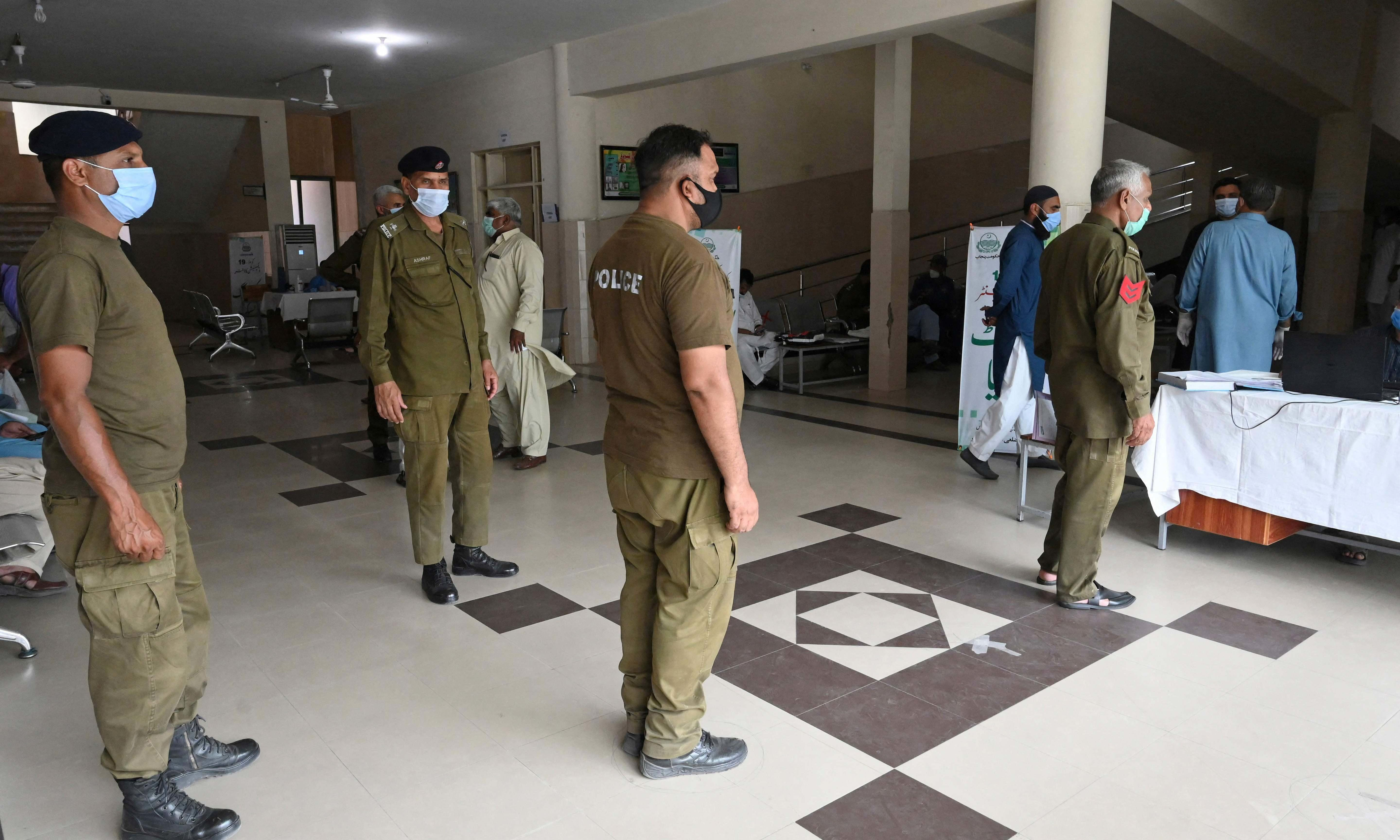 Police personnel queue up to get themselves inoculated with the Covid-19 coronavirus vaccine at a vaccination centre in Lahore on May 18. — AFP