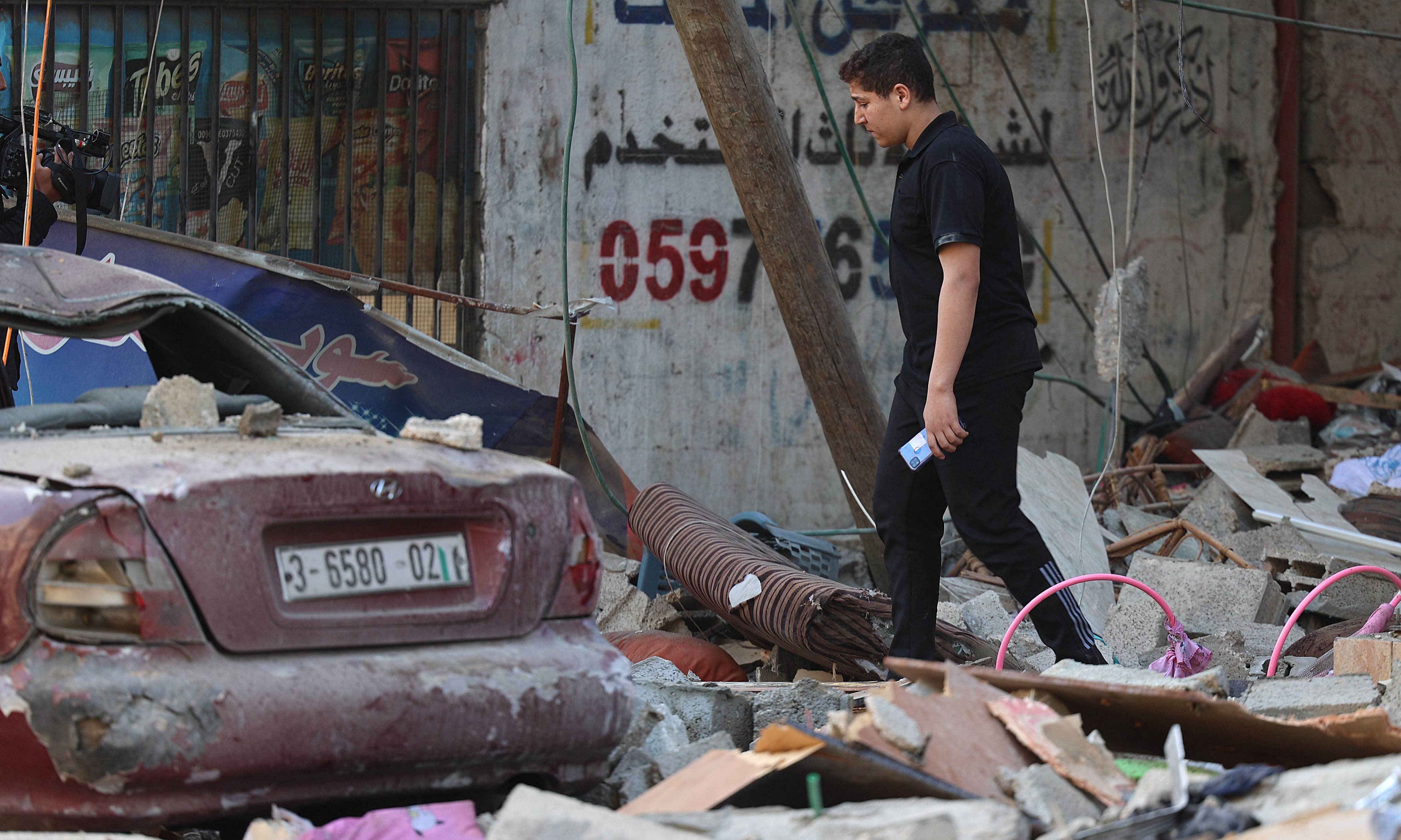 A Palestinian man walks amidst debris in the aftermath of an Israeli air strike in Gaza City, on May 19.  — AFP