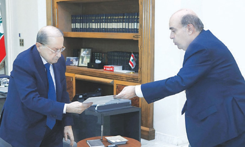 LEBANESE Foreign Minister Charbel Wehbe (right)) presenting his resignation to President Michel Aoun at the Baabda presidential palace.—AFP