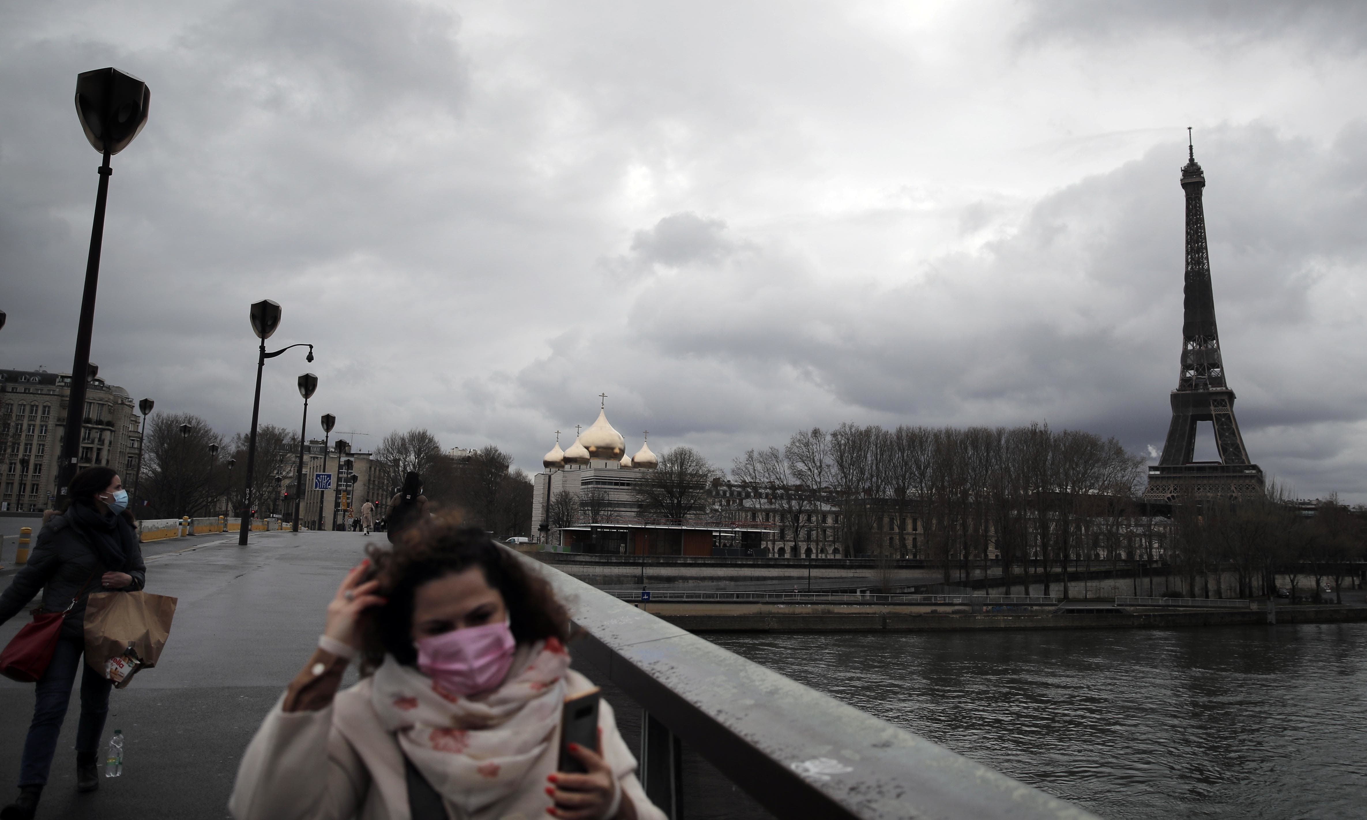 In this file photo, women cross a bridge as the Eiffel Tower is seen background in Paris. — AP