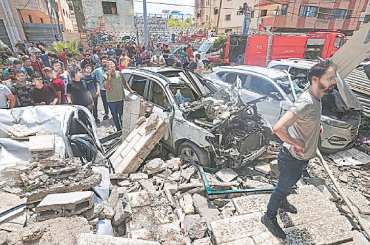 PALESTINIANS inspect a site hit by an Israeli air strike in Gaza City on Thursday. Over 250 Palestinians, including women and children, have been killed during the Israeli aggression.—AFP