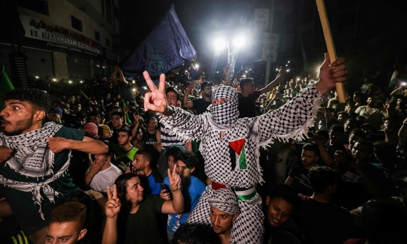 Palestinians celebrate in the streets following a ceasefire brokered by Egypt between Israel and the ruling Islamist movement Hamas in the Gaza Strip, on May 21. — AFP