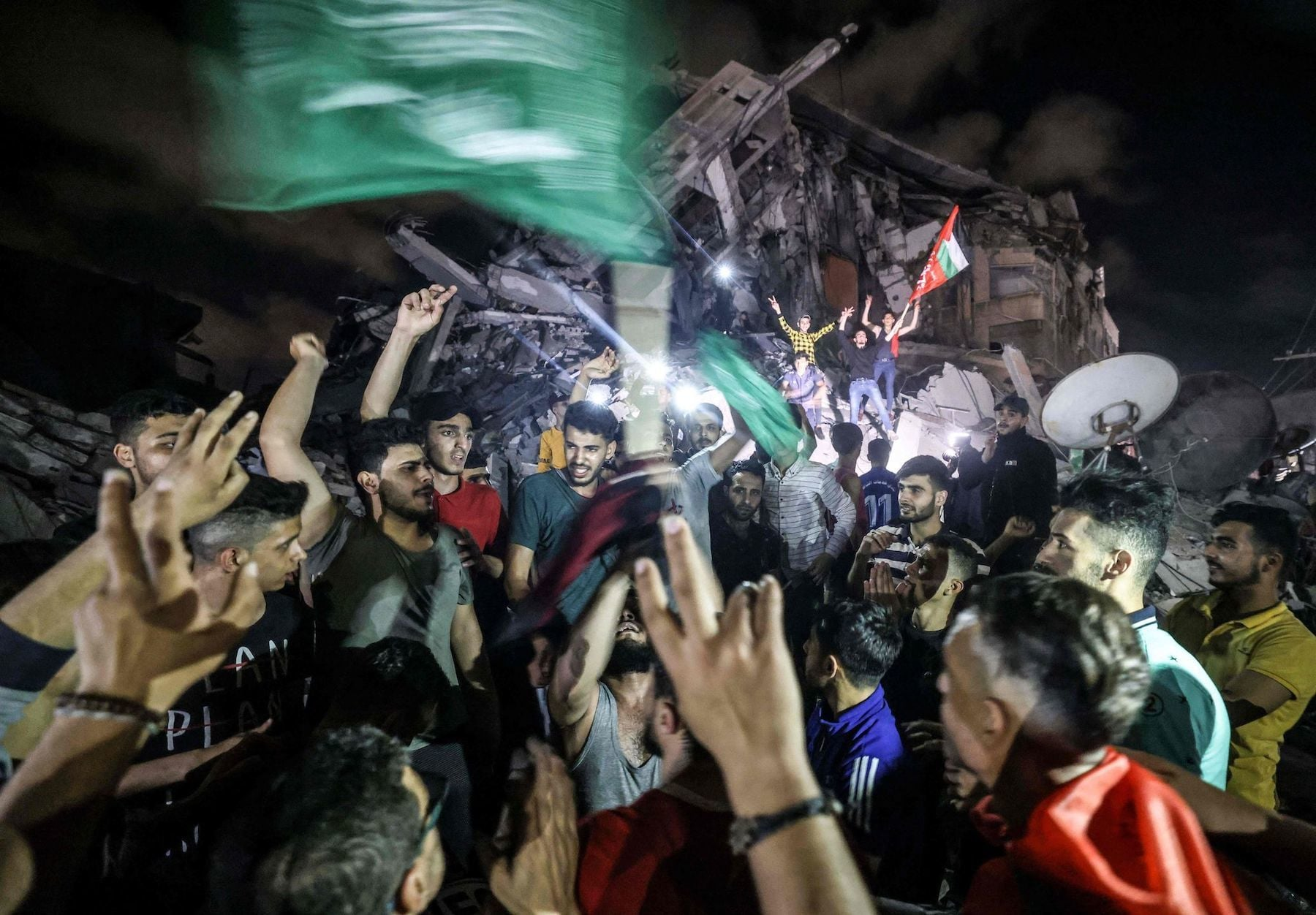 Palestinians celebrate in front of a destroyed building in Gaza City early on May 21, 2021, following a ceasefire brokered by Egypt between Israel and the ruling Hamas in the Gaza Strip. — AFP