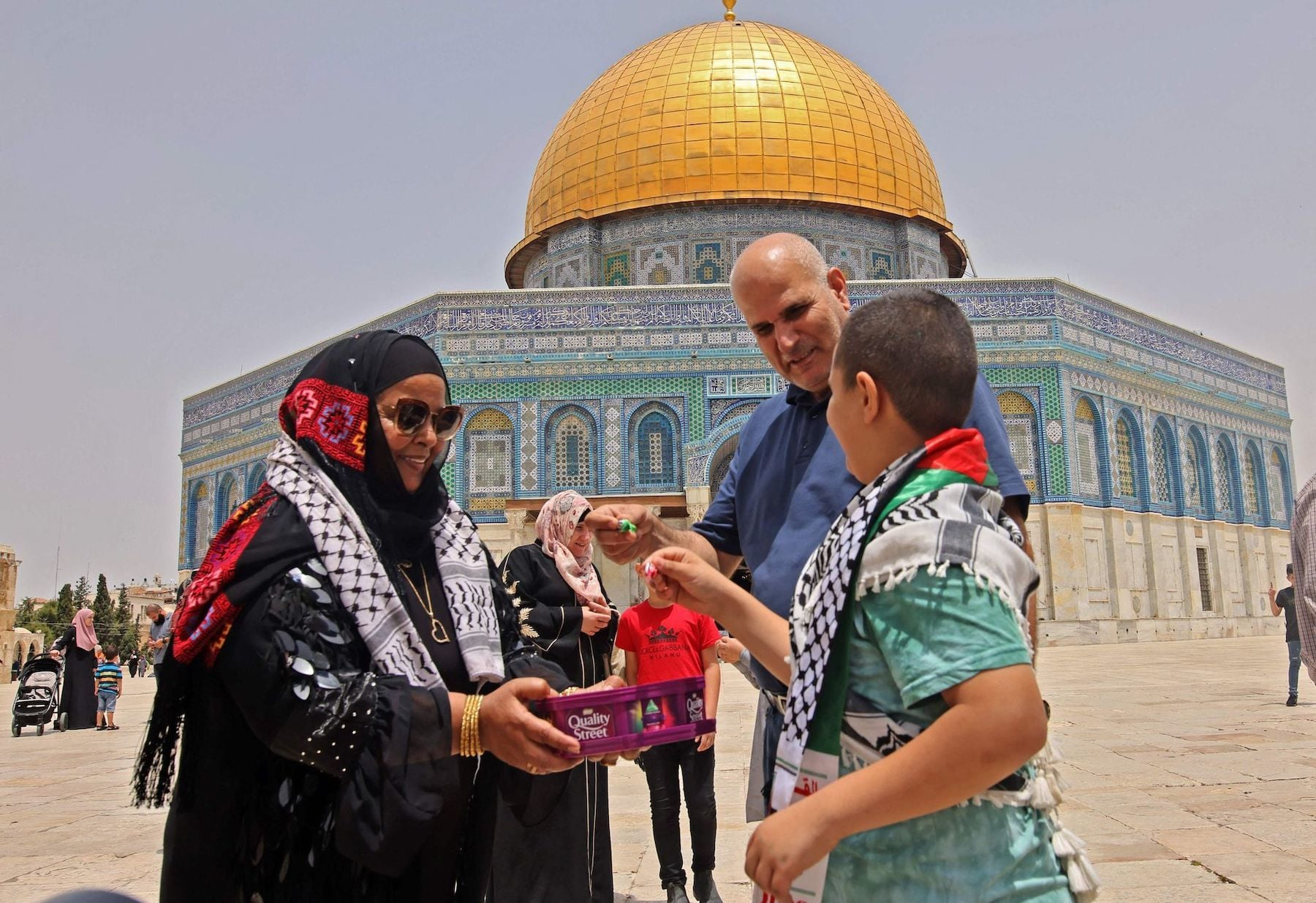 A Palestinian woman offers sweets to worshippers to celebrate the end of fighting between Israel and Hamas, during Friday prayers in Jerusalem's al-Aqsa mosque compound, the third holiest site of Islam, on May 21, 2021. — AFP