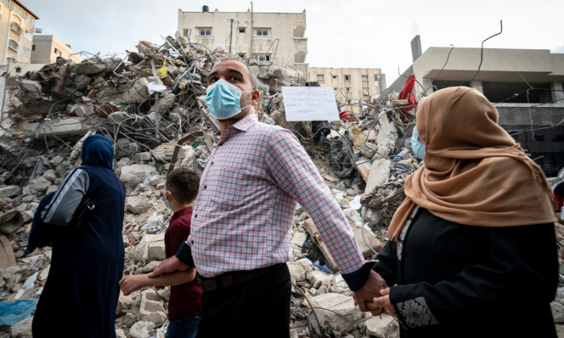 A family passes the rubble from a building previously destroyed in an Israeli air strike following a ceasefire reached after 11 days of violence, in Gaza City on Friday. — AP
