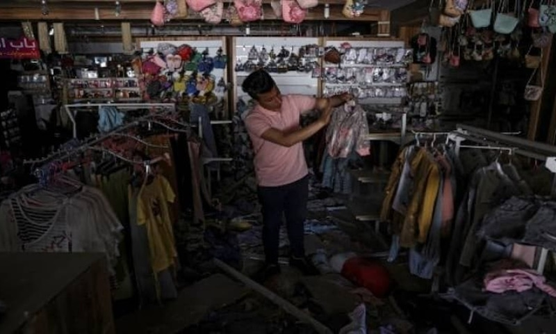 A Palestinian man inspects damaged products in a shopping centre, next to a building that was hit by an Israeli strike, in Gaza City on May 22. AFP