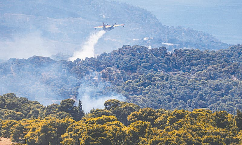 A fire fighting airplane sprays water to extinguish a wild fire on Mount Geraneia, west of Athens on Saturday. — AFP