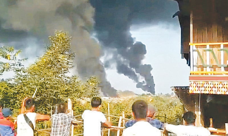 People look at thick columns of black smoke from jade mining town of Hkamti on Saturday. — Reuters