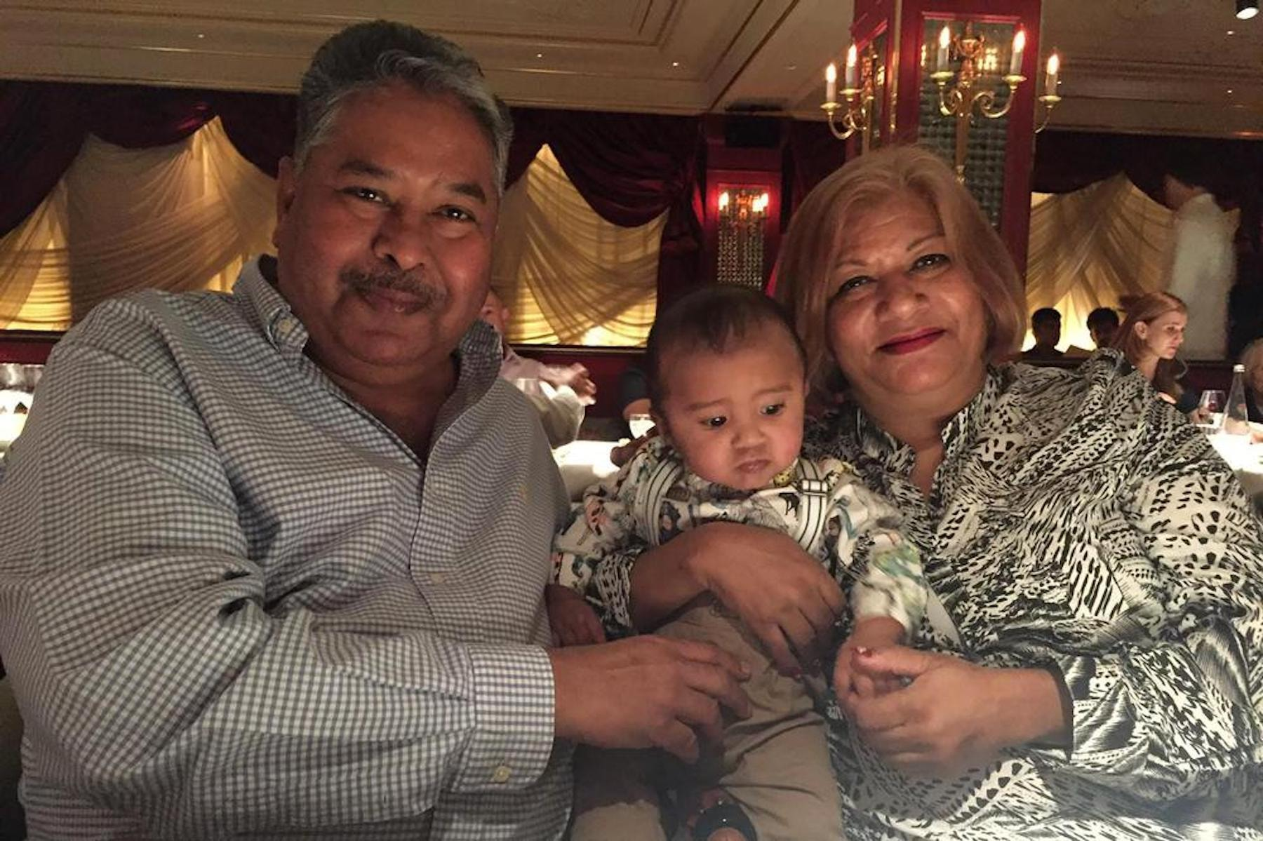In this undated photo provided by Amrohi family, Yamini Amrohi, right, poses with her grandson and late husband Ashok Amrohi, who died of Covid-19, at a restaurant in London. Ashok, a medical doctor before joining the diplomatic corps, had traveled the world. He'd been ambassador to Algeria, Mozambique and Brunei, and had retired to Gurgaon, a city just outside the capital, and a life of golf and piano lessons. — Amrohi family via AP