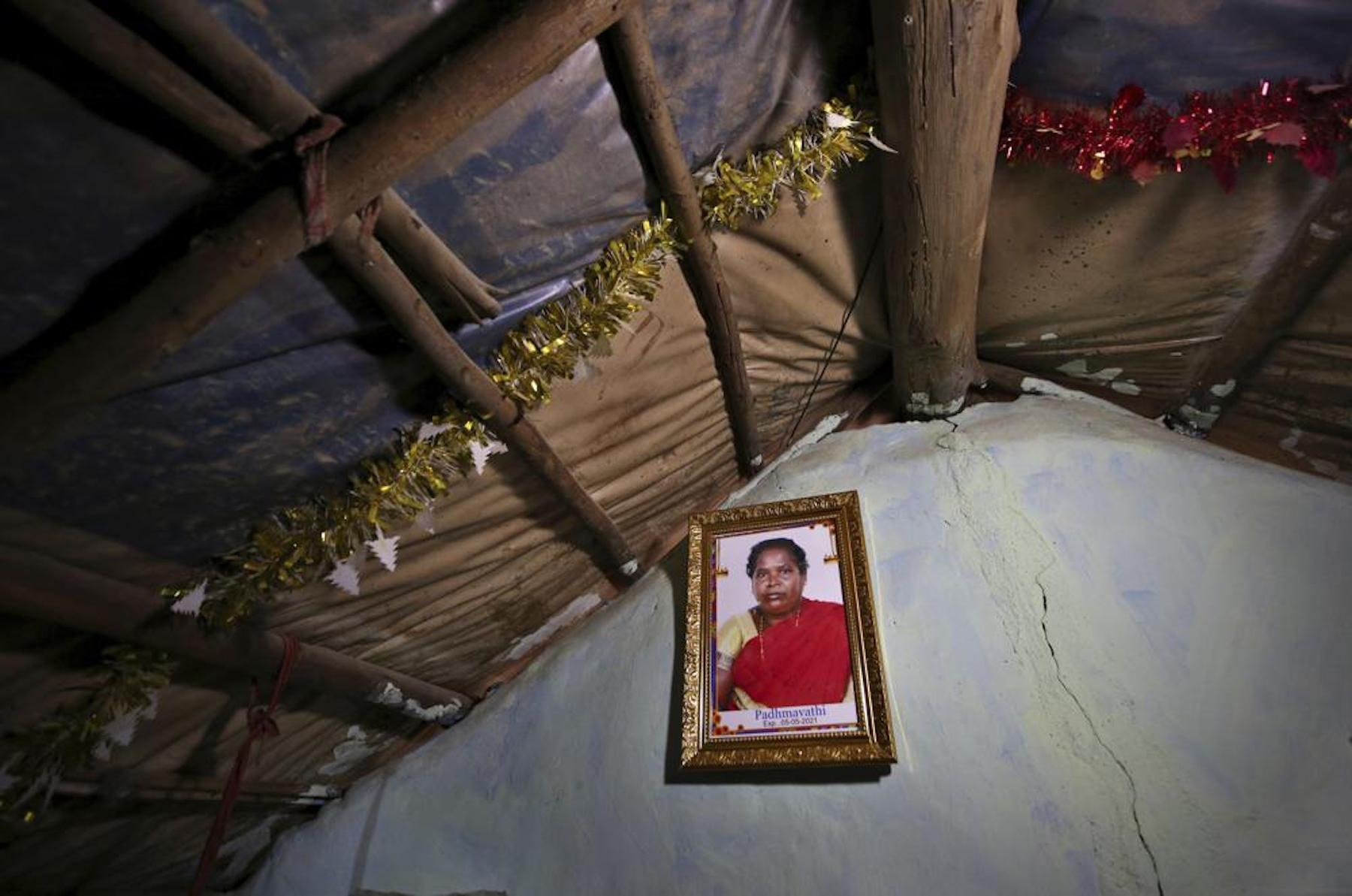 A portrait of Padmavathi, who died of Covid-19, hangs on the wall of her family hut made from bamboo and plastic sheeting in a slum in Bengaluru, India, on Thursday, May 20, 2021. Padmavathi collected hair, taking it from women's combs and hairbrushes to later be used for wigs. She earned about $50 a month. —AP