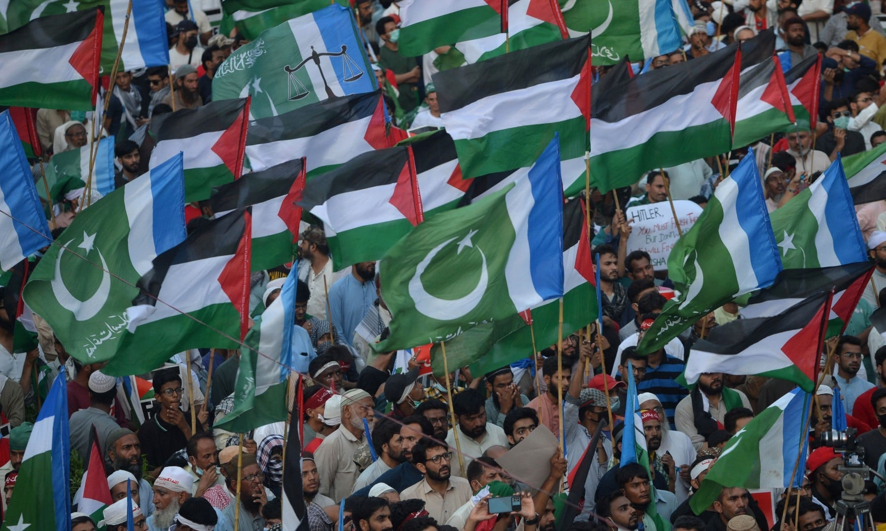 Supporters of the Jamaat-e-Islami (JI) wave Palestinian and their party flags during a protest against Israel's attacks on the Palestinian Gaza Strip in Karachi on May 23. — AFP