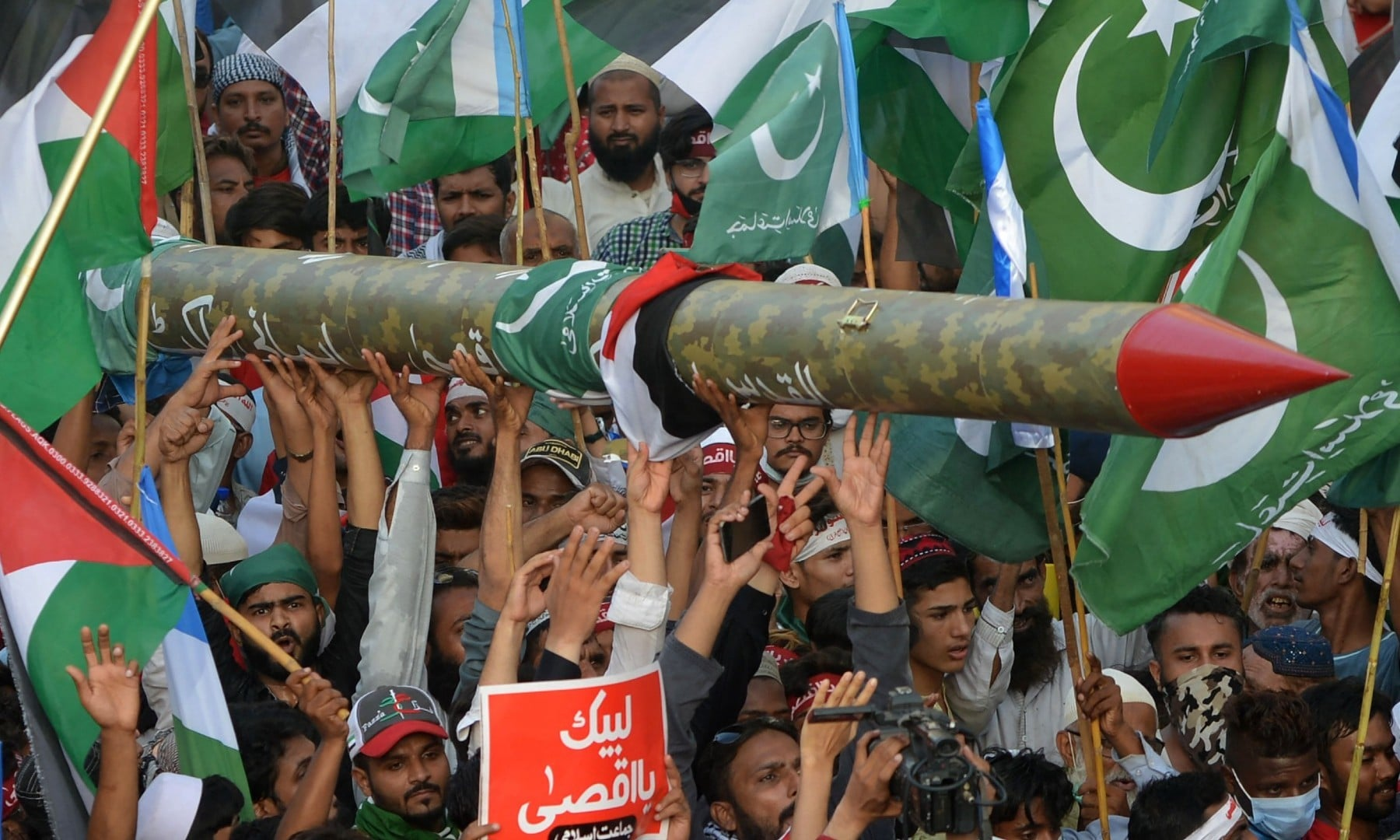 Supporters of the Jamaat-e-Islami (JI) carry a dummy rocket during a protest against Israel's attacks on the Palestinian Gaza Strip, in Karachi on May 23. — AFP