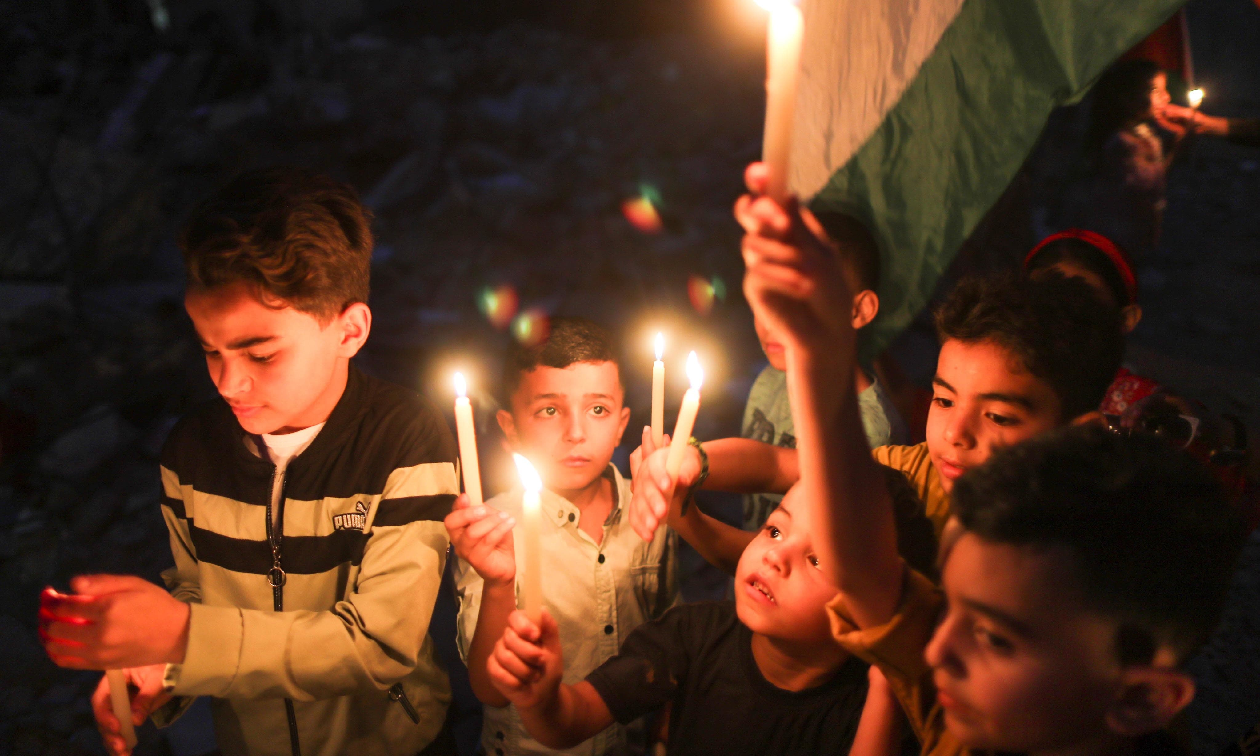 Children hold candles at the site of a house that was destroyed by Israeli air strikes, in Gaza May 23. — Reuters