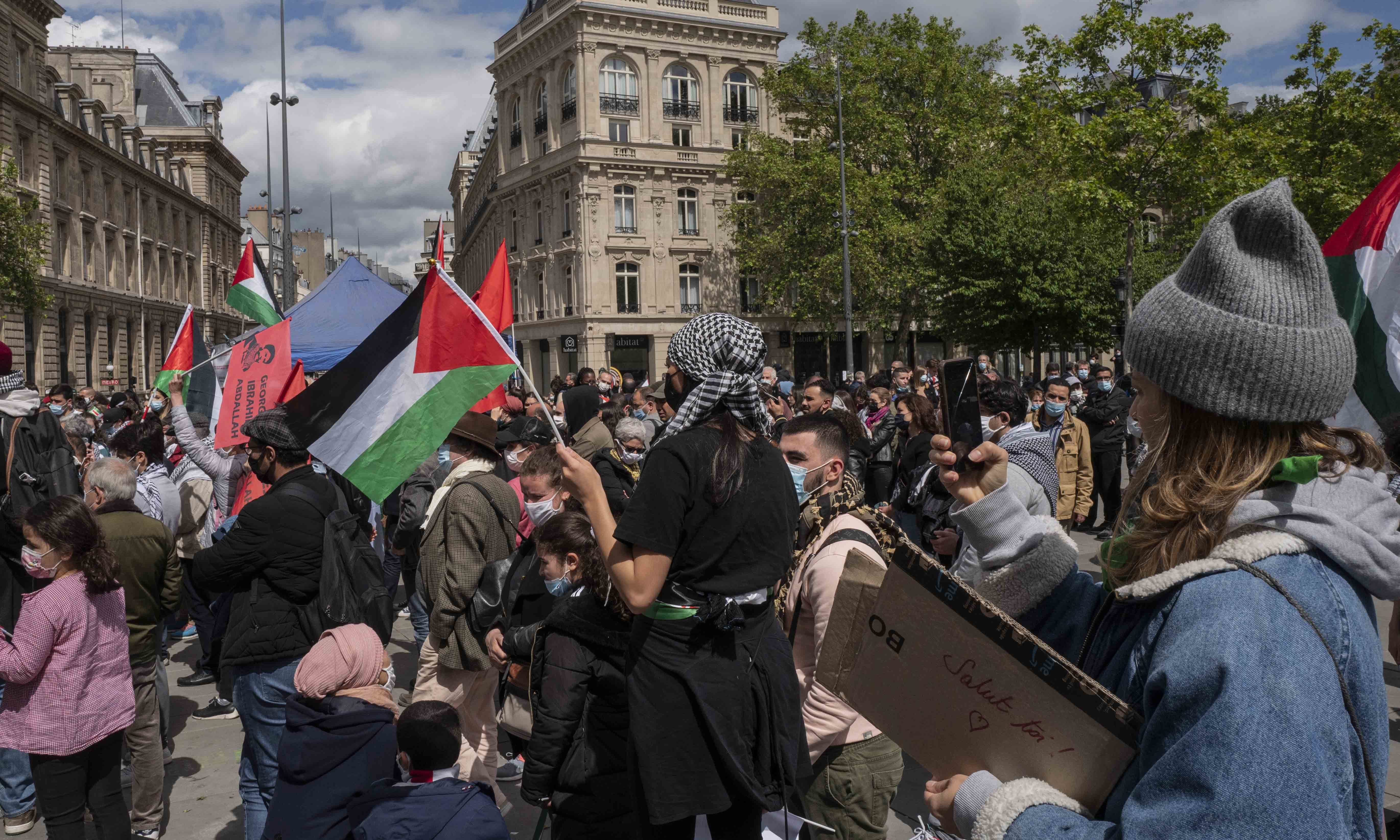 Protesters hold Palestinian flags in Paris as they take part in a rally supporting Palestinians. — AP