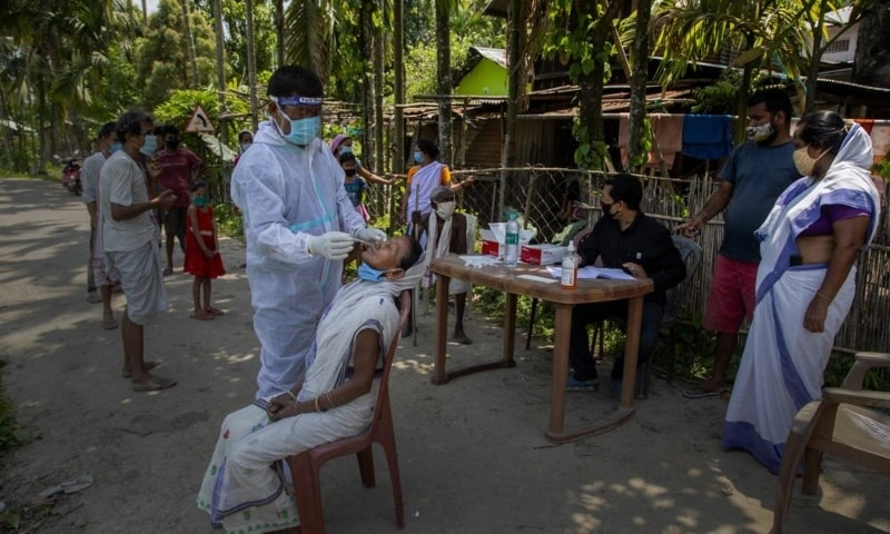 An Indian health worker in a protective suit takes the swab of a village woman to test for Covid-19 in Burha Mayong village, Morigaon district of Assam, India, May 22. — AP