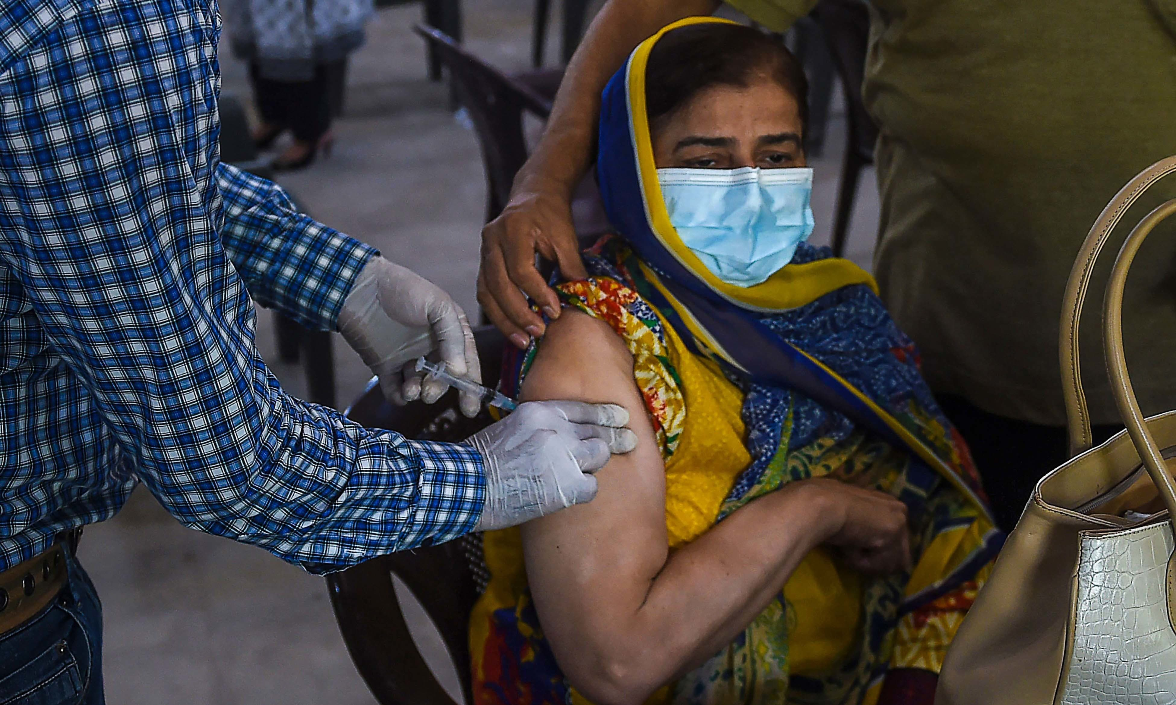 A woman receives a dose of the Covid-19 coronavirus Sinopharm vaccine at a vaccination camp in Karachi on May 25. — AFP