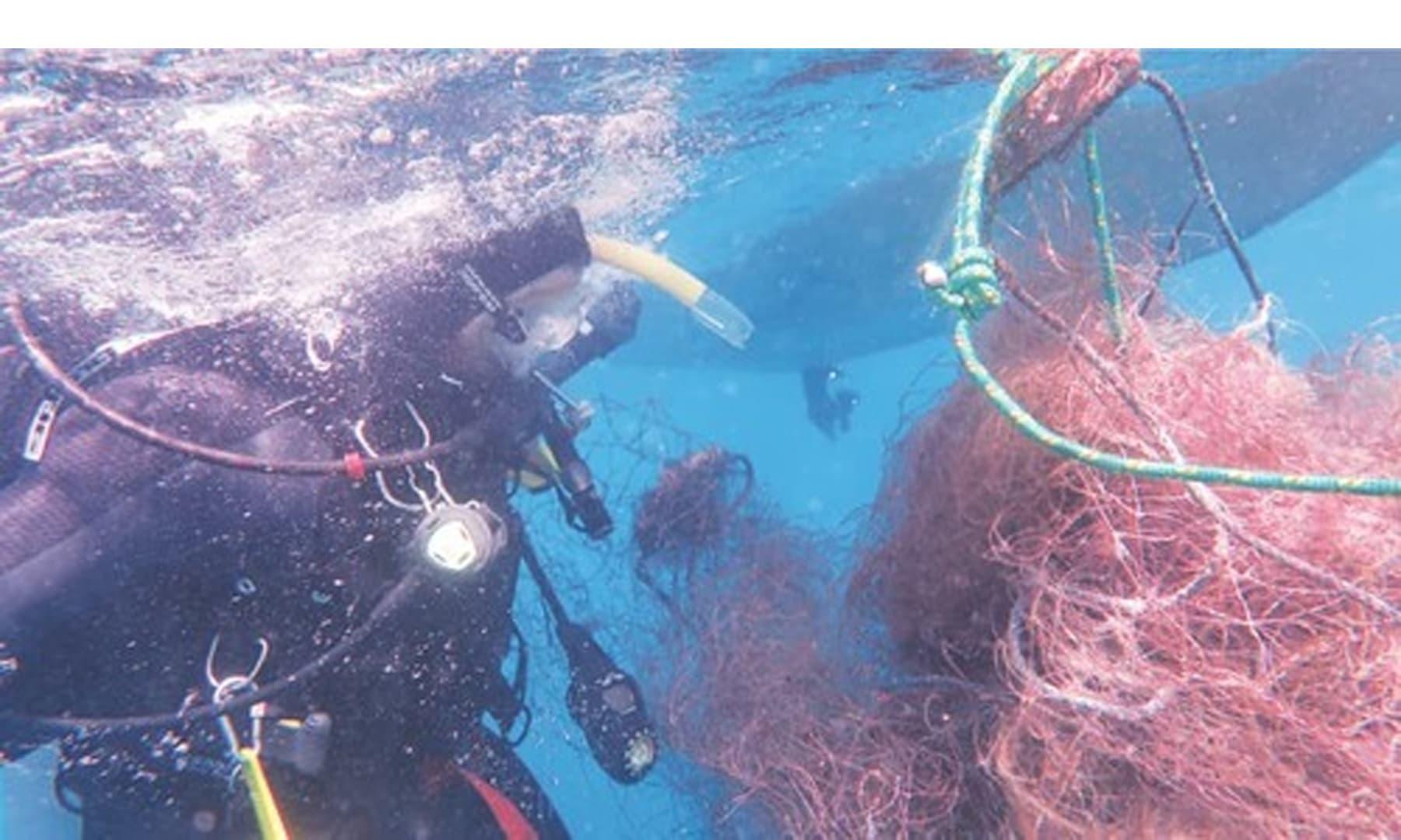گہرے پانی سے ملنے والے متروکہ مچھلی کے جالوں کو سطح تک پہنچایا جا رہا ہے— تصویر بشکریہ محمد اقبال