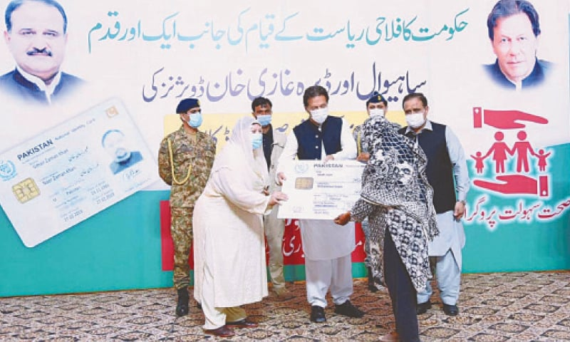 LAYYAH: Prime Minister Imran Khan and Punjab Health Minister Dr Yasmin Rashid distribute health insurance cards among the people of Sahiwal and Dera Ghazi Khan divisions on Wednesday.—APP
