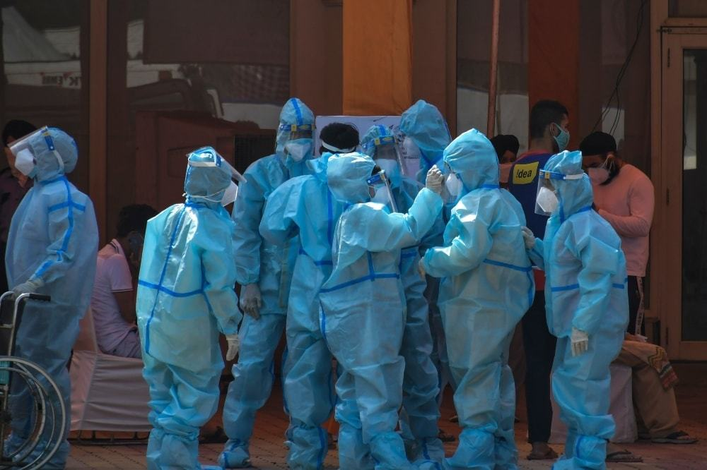 Health workers and volunteers in personal protective suits wait to receive patients outside a Covid-19 hospital in New Delhi. — AP/File