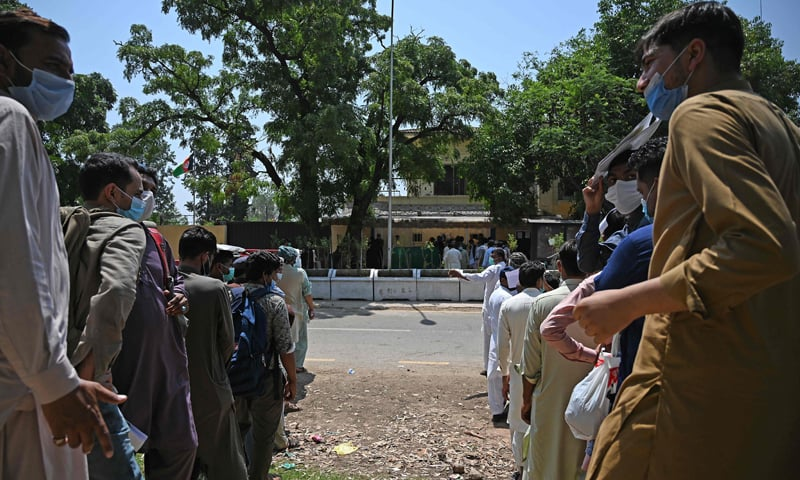In this picture taken on May 19, 2021, Pakistani nationals, wearing face masks amid concerns over the spread of the Covid-19 coronavirus, wait in a queue to apply for a visa outside Afghanistan's embassy in Islamabad. Afghanistan is experiencing an unlikely influx of visitors as a result of the coronavirus pandemic, with thousands of desperate Pakistani workers transiting through the war-torn capital in a bid to reach Saudi Arabia. — AFP
