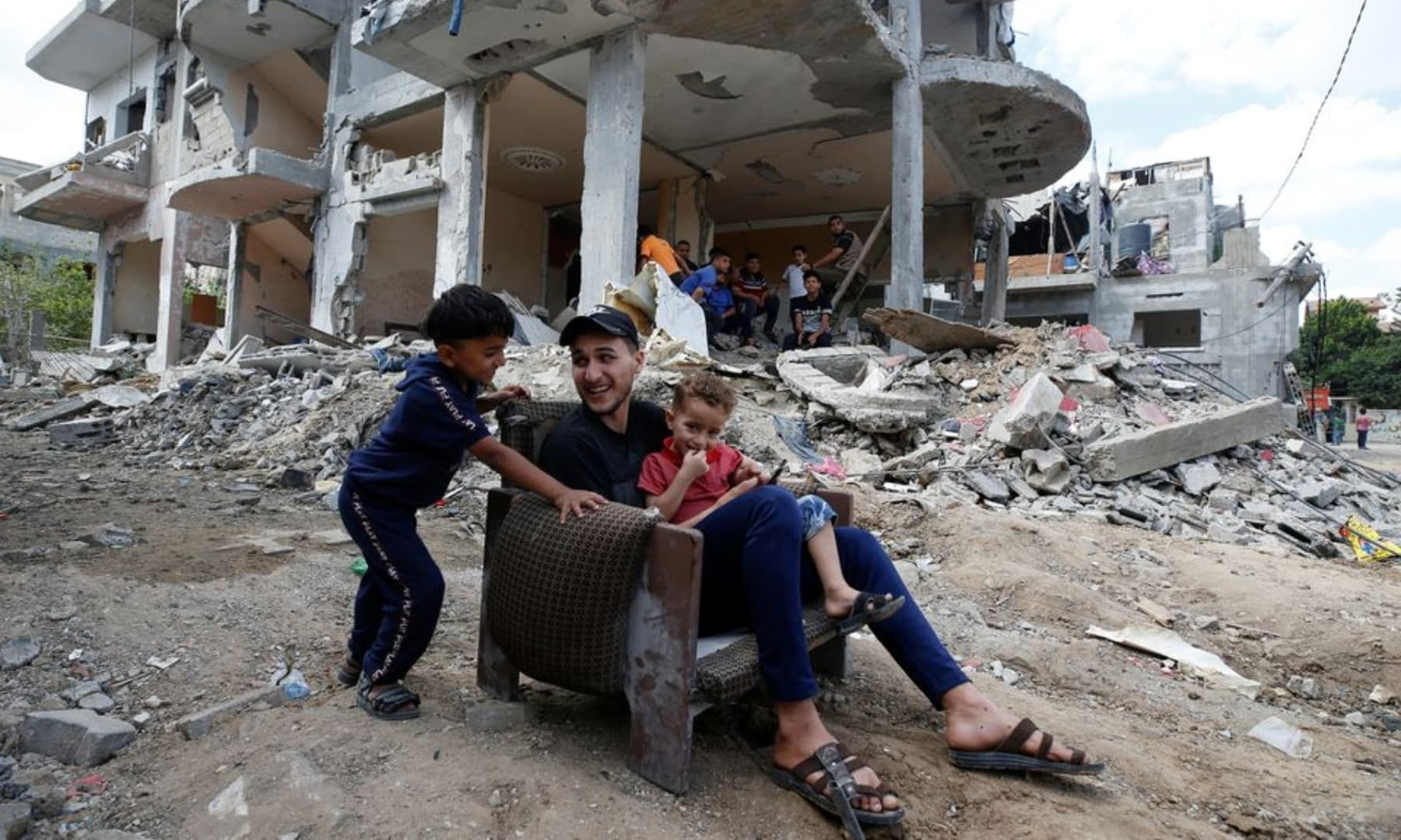 Palestinians sit on a chair amid the rubble of a building which was damaged in Israeli air strikes during the Israeli attacks on Gaza, May 23, 2021. — Reuters