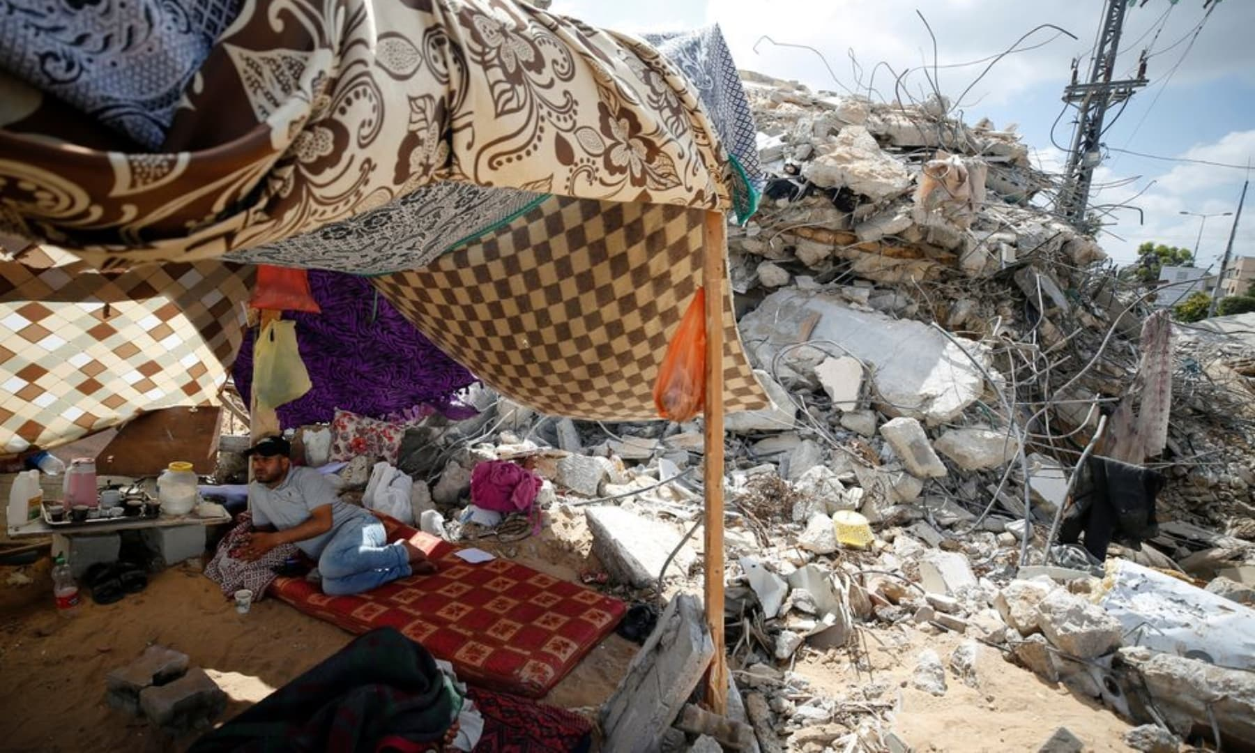 A Palestinian man sits in a makeshift tent amid the rubble of their houses which were destroyed by Israeli air strikes during the Israeli attacks on Gaza, May 23, 2021. — Reuters