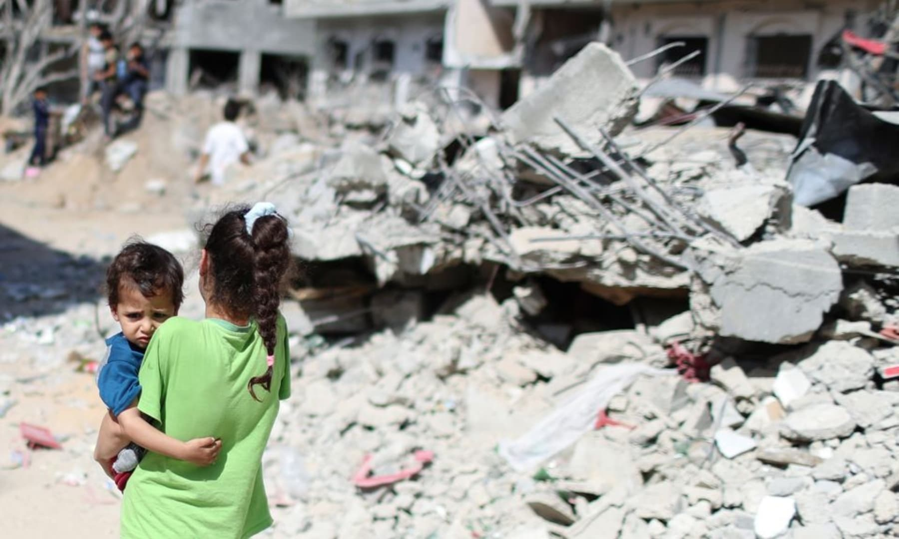 A Palestinian girl carries a boy amid the rubble of their houses which were destroyed by Israeli air strikes during the Israeli attacks on Gaza, May 23, 2021. — Reuters