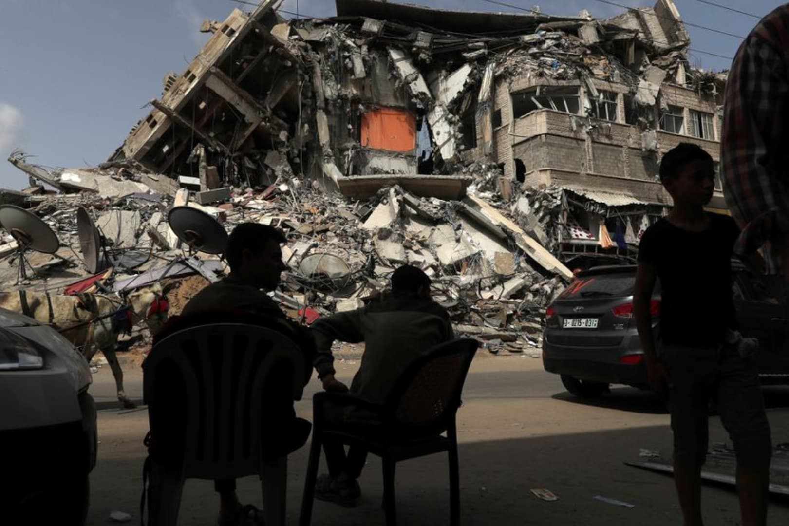 Palestinians sit near the ruins of a building destroyed in an Israeli air strike in the recent cross-border attacks by Israel on Gaza, May 21, 2021. — Reuters