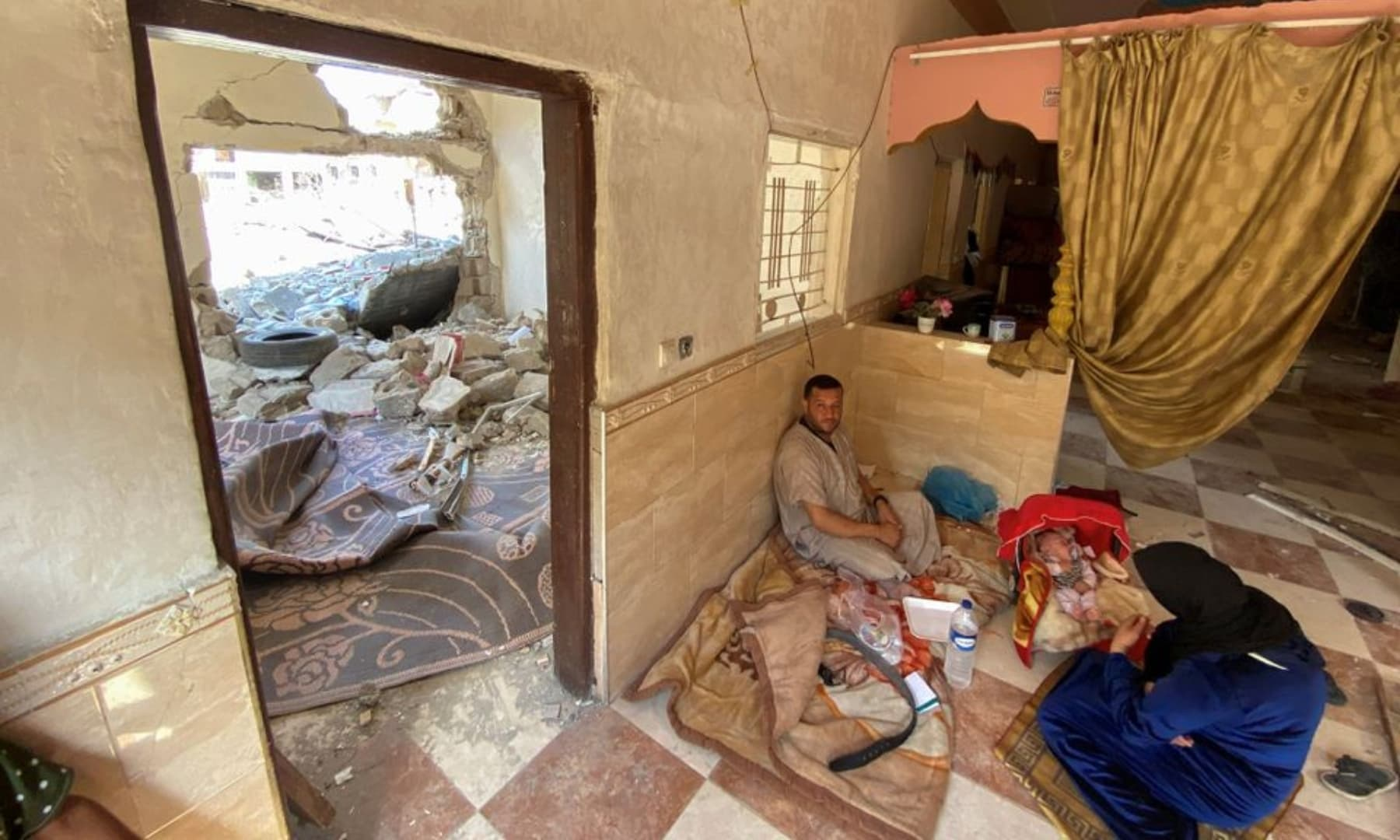 Palestinians sit inside their damaged house following Israeli-Palestinian truce, in Beit Hanoun in the northern Gaza Strip, May 23, 2021. — Reuters