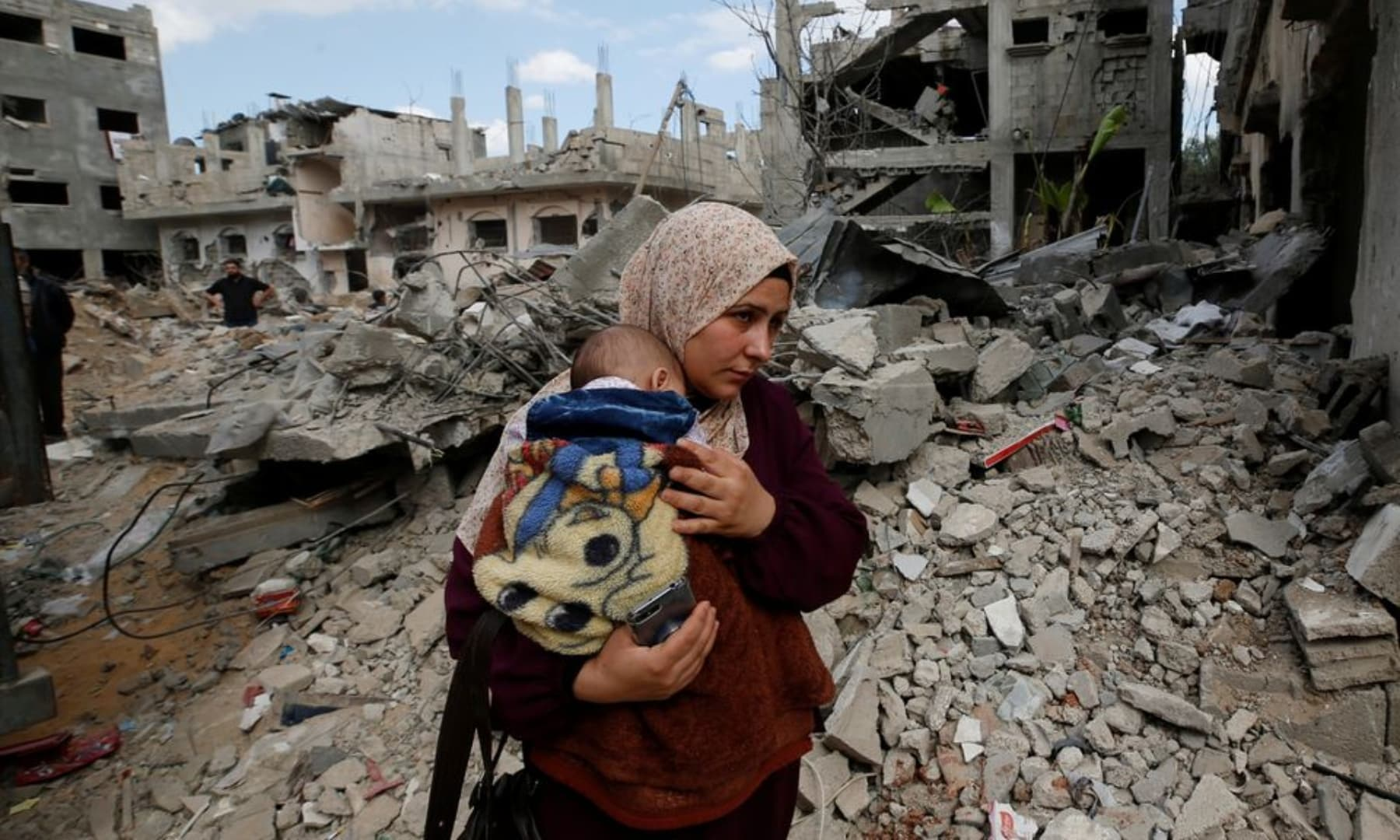 A Palestinian woman carries her child amid the rubble of their houses which were destroyed by Israeli air strikes during the Israeli attacks on Gaza, May 23, 2021. — Reuters