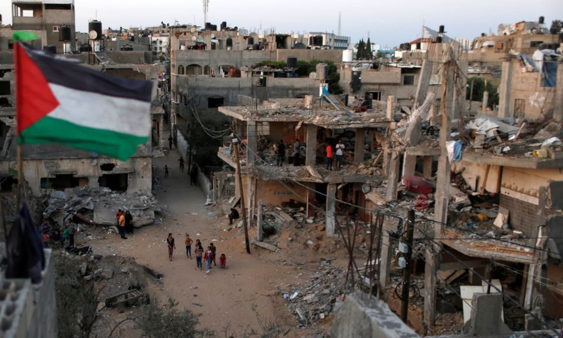 A Palestinian flag flies as the ruins of houses, which were destroyed by Israeli air strikes during the Israeli attacks on the Gaza Strip, May 25, 2021. — Reuters