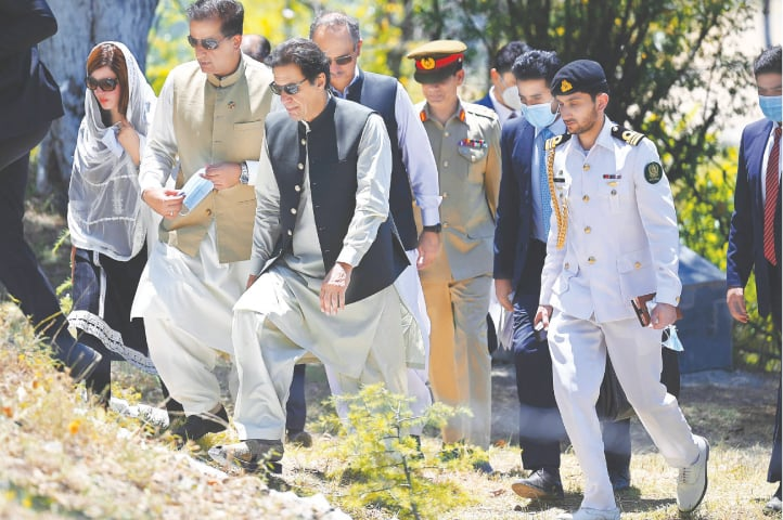 Prime Minister Imran Khan walks as he inspects the progress on the '10 Billion Tree Tsunami' project in the Makhniyal area of Haripur district on Thursday.—AFP