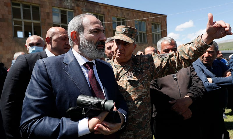 This handout photograph, taken and released by The Armenian Government Press Service on May 27, 2021, shows Armenian acting Prime Minister Nikol Pashinyan (L) as he speaks with a serviceman in the village of Gegharkunik, near the site where six Armenian servicemen were captured. — AFP