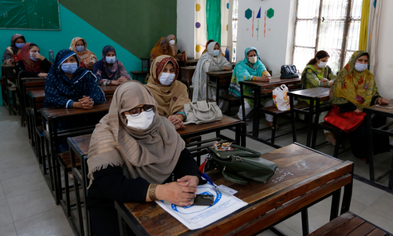 Teachers wait their turn to receive the first shot of the Sinovac coronavirus vaccine at a school in Lahore on Friday. — AP