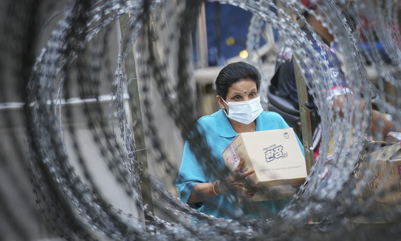 A resident wearing a face mask collects a package behind barbed wire outside the Pangsapuri Permai housing, which is placed under the enhanced movement control order due to the drastic increase in the number of Covid-19 cases recorded over the past 10 days in Malaysia. Malaysia's latest coronavirus surge has been taking a turn for the worse as rising numbers and deaths have caused alarm among health officials, while cemeteries in the capital are dealing with an increasing number of deaths. — AP