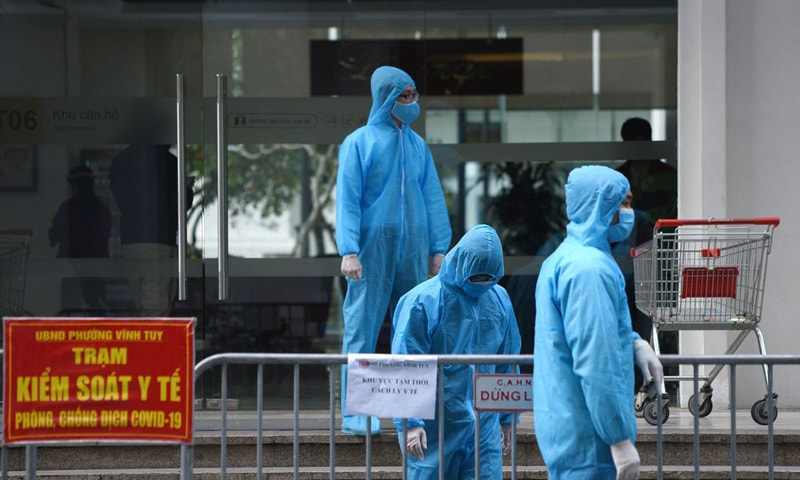 Medical workers in protective suits stand outside a quarantined building amid the Covid-19 outbreak in Hanoi, Vietnam. — Reuters
