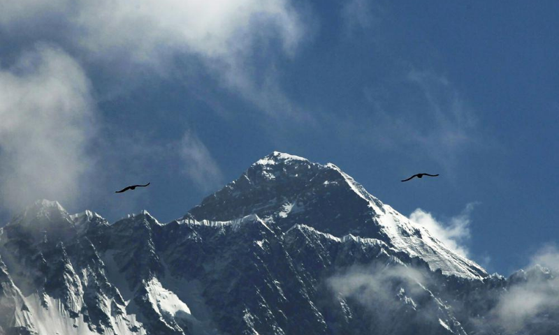 Birds fly as Mount Everest is seen from Namche Bajar, Solukhumbu district, Nepal. — AP