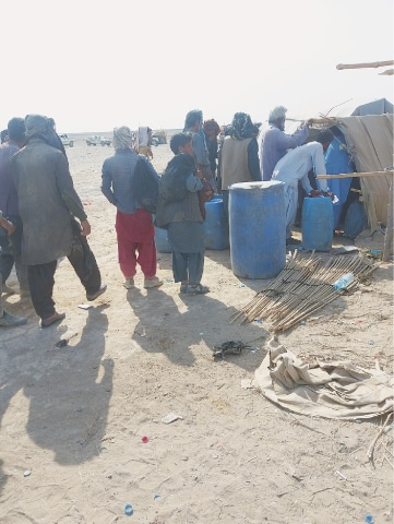Travellers line up to buy cold water and other necessary items from a pop-up store in the desert