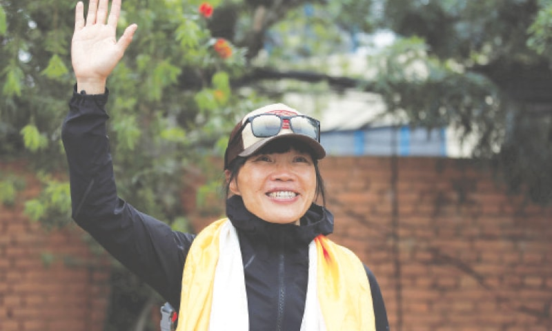 TSANG Yin-Hung waves for a picture upon her return to Kathmandu after climbing Everest.—Reuters