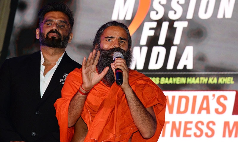 Bollywood actor Suniel Shetty (L) and yoga guru Baba Ramdev speak to media during a promotional event in New Delhi. Thousands of angry doctors across India wore black armbands on June 1, 2021, demanding the arrest of the hugely popular guru for claiming conventional medicine had killed thousands of coronavirus patients. — AFP/ File