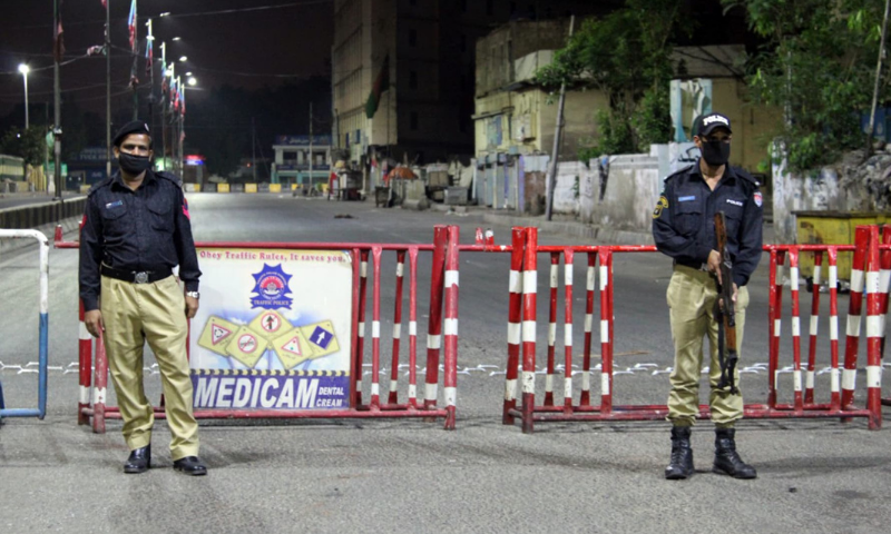 Policemen stand at a blocked road in Karachi. — Photo by Shahzeb Ahmed/File